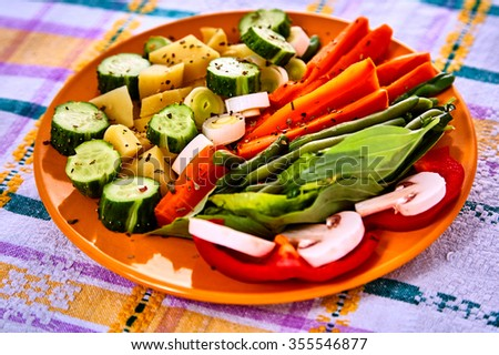 Ladle of steamed freshly harvested young vegetables including crinkle cut sliced carrots, peas and potato batons for a healthy accompaniment to dinner