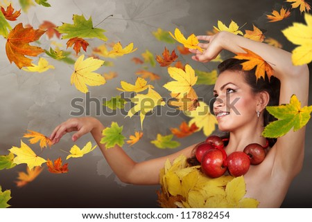 Lady Autumn in swirling falling leaves - stock photo