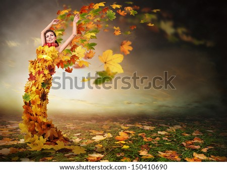 Lady Autumn with wings from falling leaves - stock photo