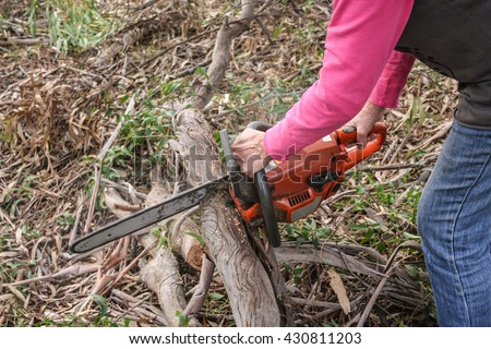 Lady cutting a branch for firewood with orange chainsaw.