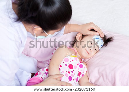 Lady doctor touching forehead little asian girl,girl lying on sickbed - stock photo