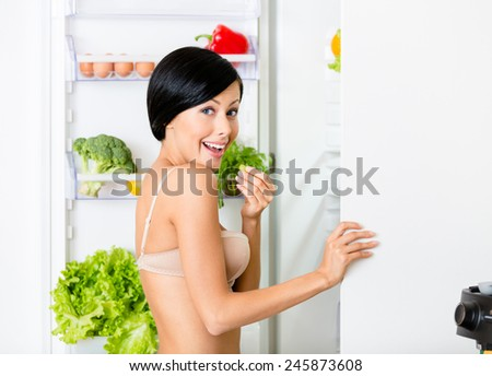 Lady eating near the opened fridge full of vegetables and fruit. Concept of healthy and dieting food - stock photo