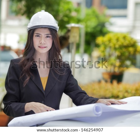 Lady engineer read an drawing in construction site