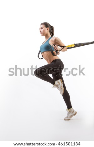 Lady exercising upper body on TRX in studio. Low view of beautiful young lady posing for photographer while training suspension trainer sling. Studio shot.