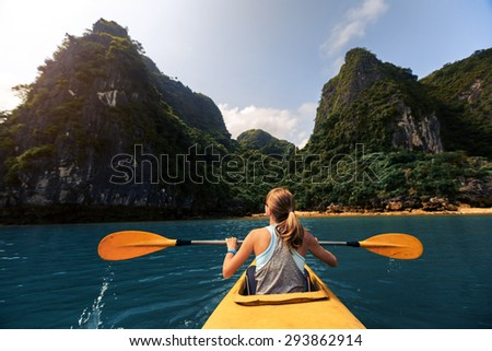 Lady exploring Ha Long Bay (UNESCO World Heritage Site) by kayak. Vietnam - stock photo