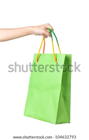 Lady hand holding green paper shopping  bag with  beautiful  color rope handle on white background