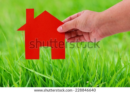 lady hand holding red home paper cut on green grass background