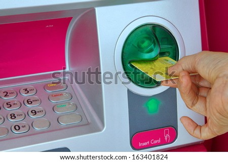 Lady hand inserting card into an pink ATM to begin a financial transaction - stock photo