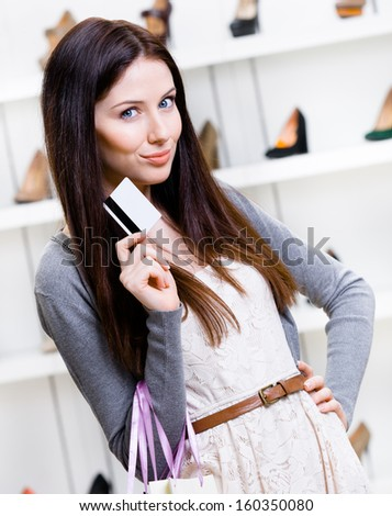 Lady hands credit card in footwear shop with great variety of stylish shoes - stock photo