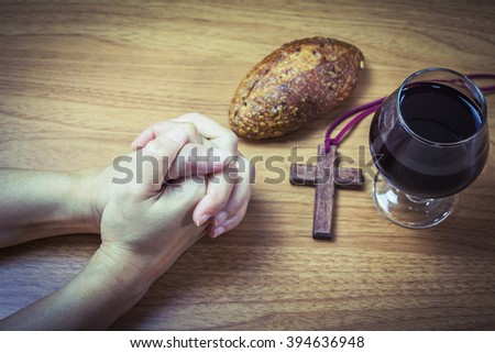 lady hands praying on wooden table  with a cup of grape juice, bread and  wooden cross, communion concept, Easter background - stock photo