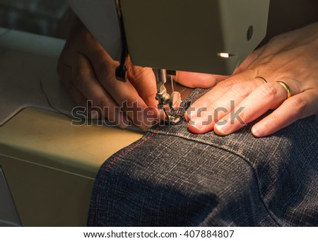 lady  hands sewing her cloth with the light of sewing machine, close up
