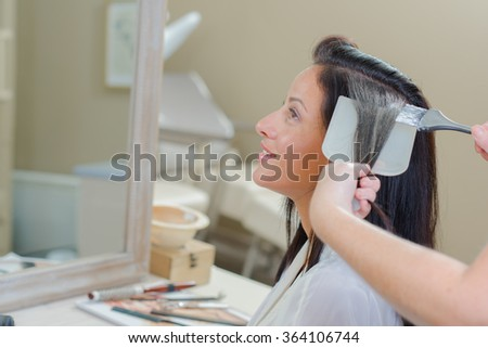 Lady having hair dyed - stock photo