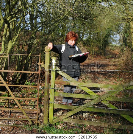 Lady Hiker leaning on a fence reading a map - stock photo