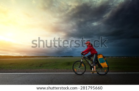Lady hiker riding loaded bicycle on a paved asphalt road with dark storm clouds on the background - stock photo