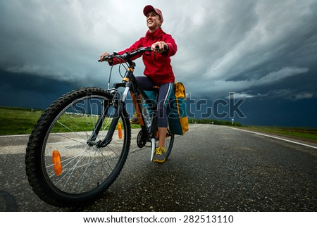 Lady hiker riding loaded bicycle on the paved asphalt road with stormy clouds on the background - stock photo