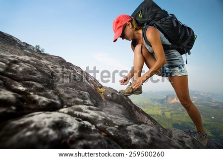 Lady hiker with backpack standing on slope of the mountain and tying shoelace - stock photo