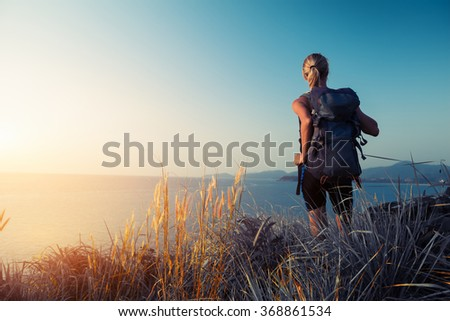 Lady hiker with backpack standing on the green meadow and enjoying sea view