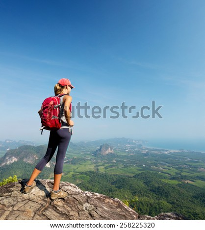 Lady hiker with backpack standing on top of the mountain - stock photo