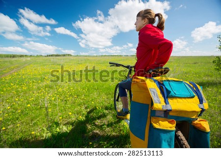 Lady hiker with loaded bicycle relaxing on a green summer meadow