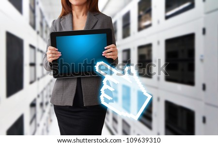 Lady hold digital touch pad in data center room and digital hand point to her - stock photo