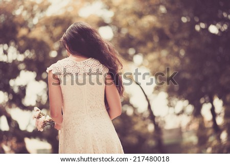 Lady in a lace dress with flowers in her hands, rear view - stock photo