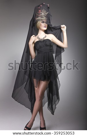 Lady in a short black dress posing with a long veil attached to a fashionable hat decorated with flowers
