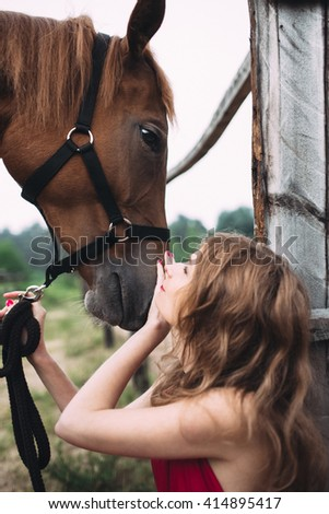 Lady in beautiful dress embraces her horse