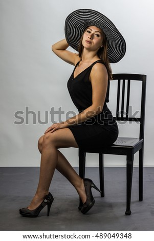 lady in black with long hair and chapeau sitting on chair of black