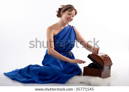 Lady in blue antique dress opening box on white background