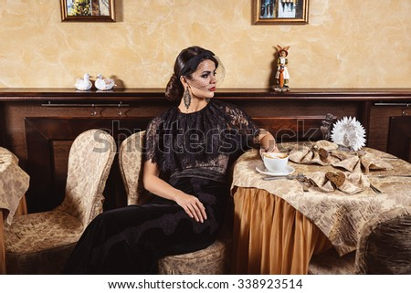 Lady in evening dress at a table in a cafe.