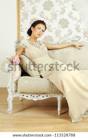 Lady in evening gown on royal sofa - stock photo