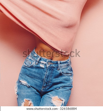 Lady in fashionable Jeans vintage style stands in pink wall