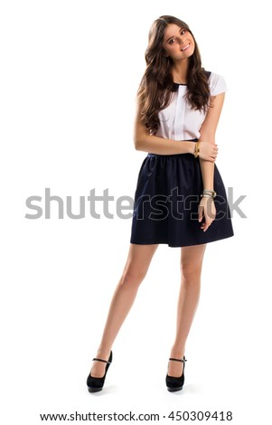 Lady in navy skirt smiling. Blouse with skirt and heels. Suede footwear and expensive bracelets. Youth, style and beauty.