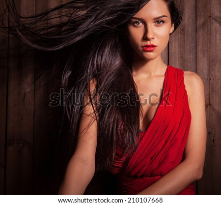 Lady in red dress pose on wooden background. - stock photo