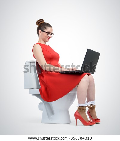 Lady in red is using laptop while seated on toilet. - stock photo