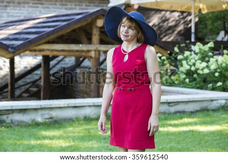 Lady in red wearing blue retro hat - stock photo