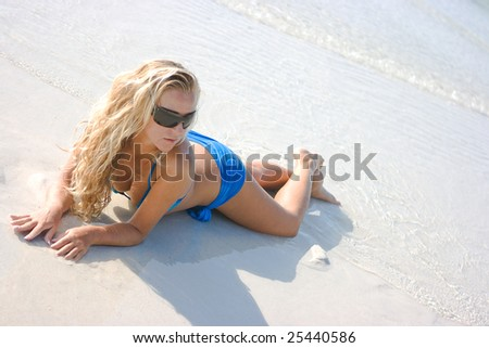Lady in sunglasses lying in the surf