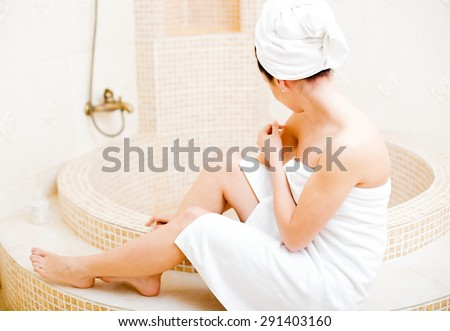 Lady in white towel sitting next to the bath tub. - stock photo