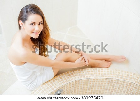 Lady in white towel sitting next to the bath tub.