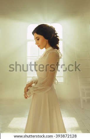 Lady in white vintage dress standing in a large spacious room , fantastic shot, fairytale princess turned into smoke , trendy toning , creative computer colors  - stock photo