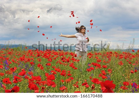Lady jumping and spreading poppies petals in the air - stock photo