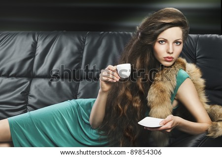 lady laying down on sofa keeping and drinking from a little cup of coffee. wearing green dress. she is lying on the sofa, looks in to the lens and takes a cup hand and saucer with left hand. - stock photo