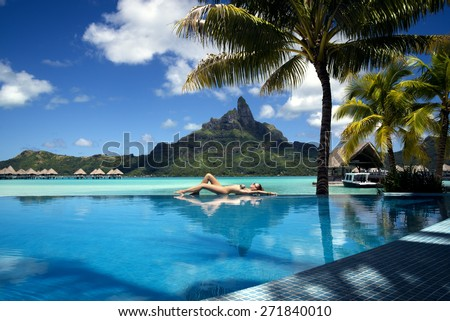lady laying on the edge of infinity pool  on the beach of a luxury vacation resort with view on the Otemanu mountain on the tropical island of Bora Bora, near Tahiti, French Polynesia, Pacific ocean - stock photo