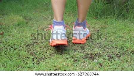Lady legs in footwear steps on the grass