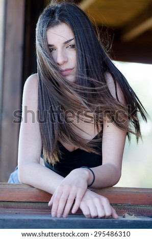 Lady looking out the window of a cabin, the wind blowing her hair