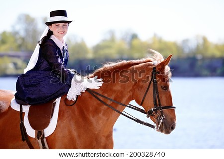 Lady on a  horse. The lady on riding walk. Portrait of the horsewoman. The woman astride a horse. The aristocrat on riding walk. - stock photo