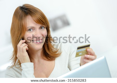 Lady on cellphone, holding credit card