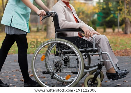Lady on wheelchair and nurse from the outside - stock photo