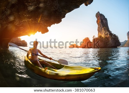 Lady paddling kayak in the tropical sea near the rock with underwater view of the sea