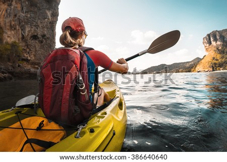 Lady paddling the kayak in the calm bay with limestone mountains